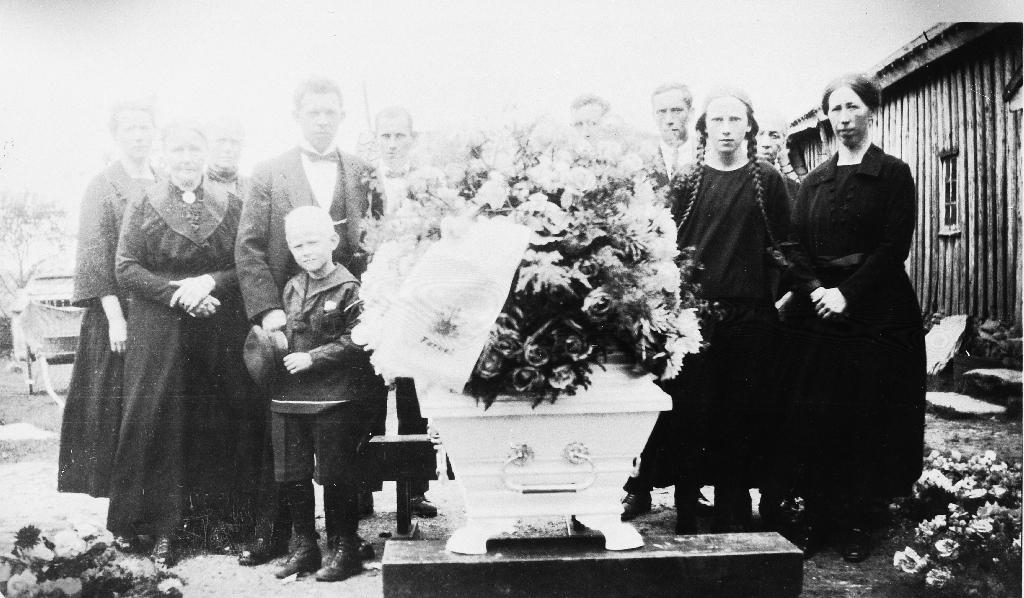 Frå gravferda til Olga (Time) Auglend (27.1.1893 - 7.8.1926). Kista står ute på tunet med næraste familie samla. Til v. står Rasmus Auglend (22.5.1891 - ) med sonen Reidar Auglend (8.1.1920 - 19.4.1997). Til høgre for Rasmus står Ingolf Time, til høgre for kista Abraham I. Time, Arne Time, Anna Time med flettene, bak henne skimtar ein Ane Bergitte Time, Elisabeth Time. Personane til v. for Rasmus kjenner eini ikkje namna på.