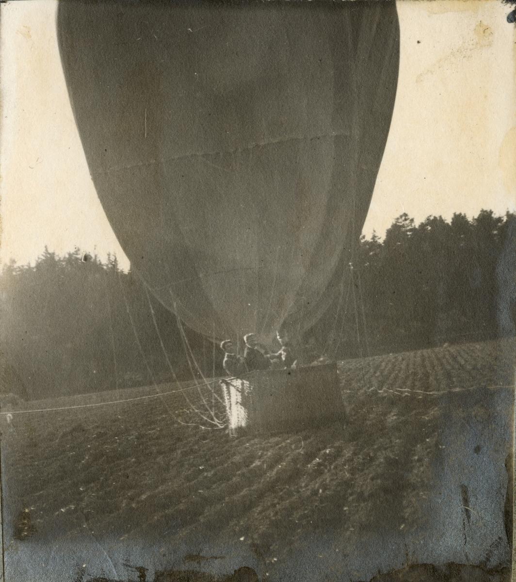 Tre män i luftballong som landat på åker.