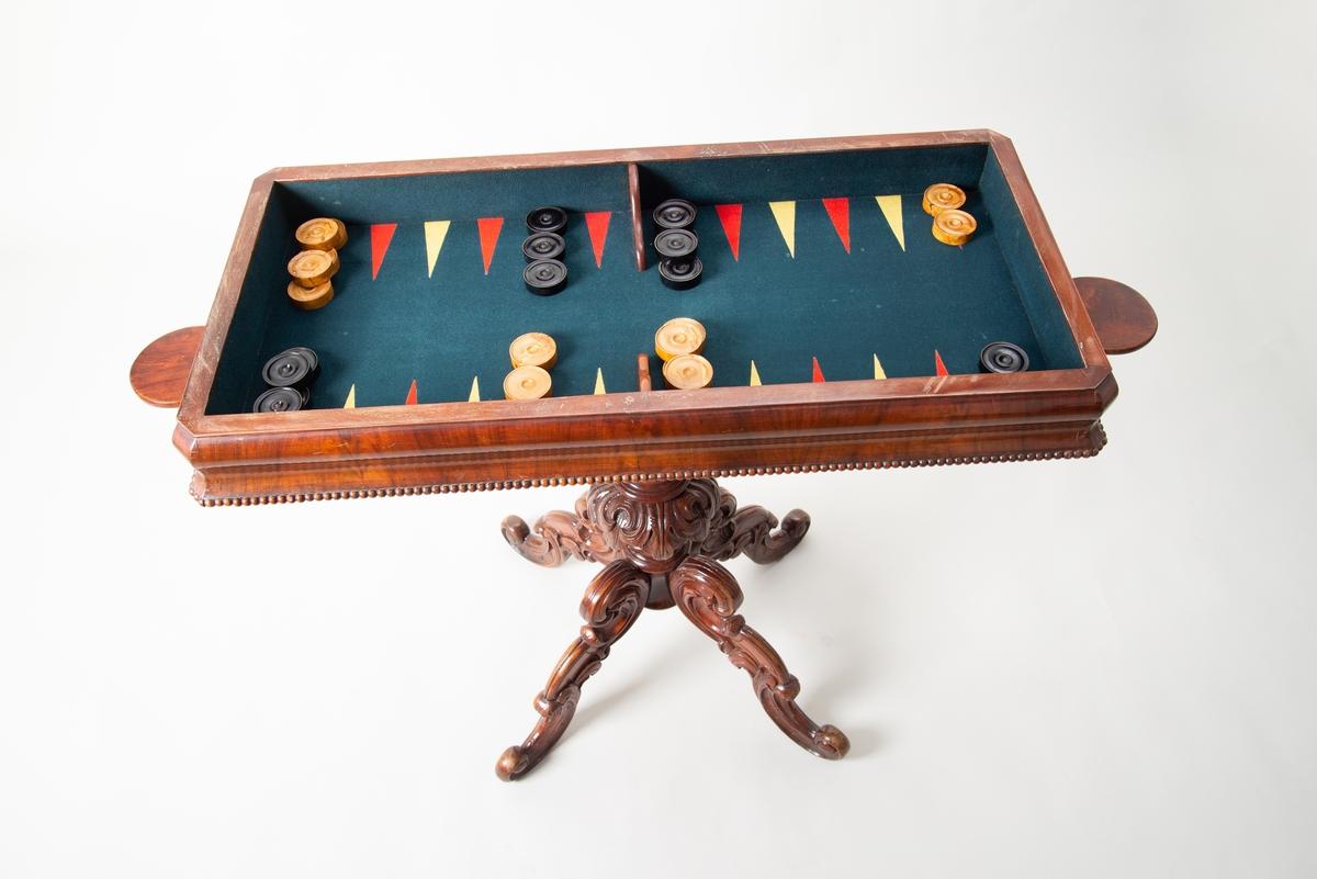 Rektangulärt spelbord av mahogny. Överst en dubbelvikt skiva av mahogny som kan tas bort - sitter fast med en grov skruv som under bordet fästs med mutter och bricka. Under skivan ett filtklätt inrede, med brädspel - spelplan av backbammon. På sargen pärlstavsdekor. Undertill två runda utfällbara brickor av mahogny (för ljus, glas eller liknande). Rikt snidad, fyrdelad pelarfot. Nyrokoko.  På spelplanen två olika uppsättningar runda spelmarker av trä, svarta och trävita. De lägre har 16 svarta, men bara 15 trävita. De högre har 14 svarta och 15 trävita. Vid backgammon används 16 spelmarker av varje färg.