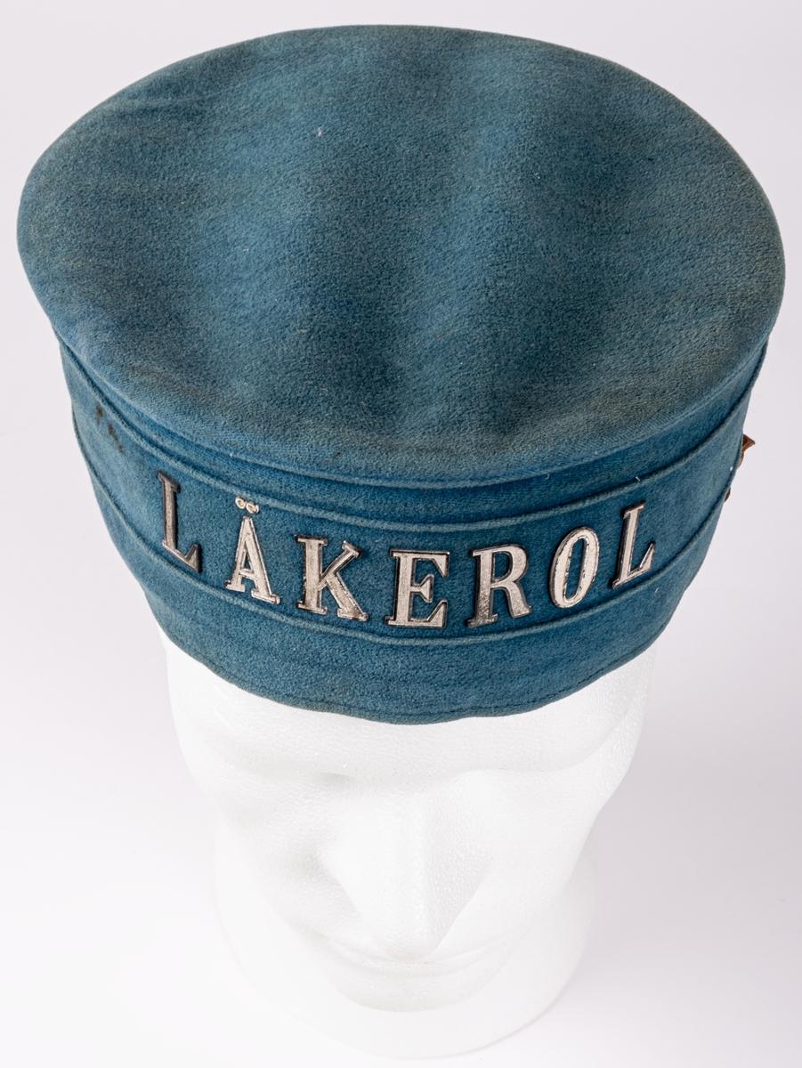 """Hatt i blå sammet med text i metall: """"LÄKEROL""""."""