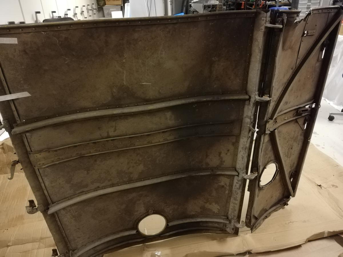Hengslet luke bestående av to deler. På begge deler er det en rund åpning ca 16 cm i diameter. Sannsynligvis motordeksel.