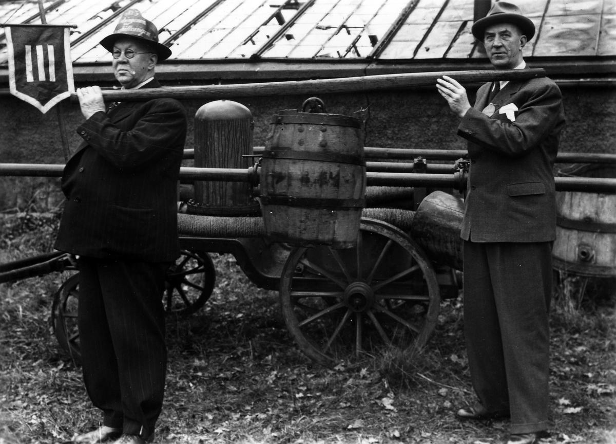 Målaremästare Georg Karlborg till vänster och brandschef Anders Hedén till höger poserar med gamla brandredskap.