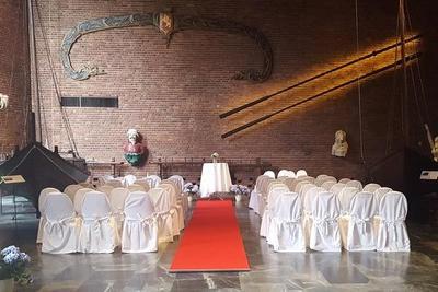 Sentralhallen i museet klargjort til bryllup, flere rader med hvitkledde stoler, en rød løper leder opp til et alter.