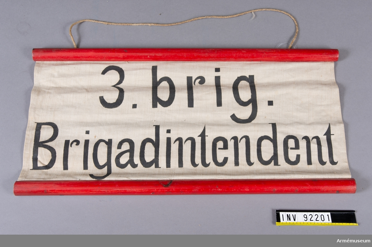 """Skylt av tyg  fäst i rödmålade träpinnar på långsidorna. Svart text: """"3. brig. Brigadintendent"""""""