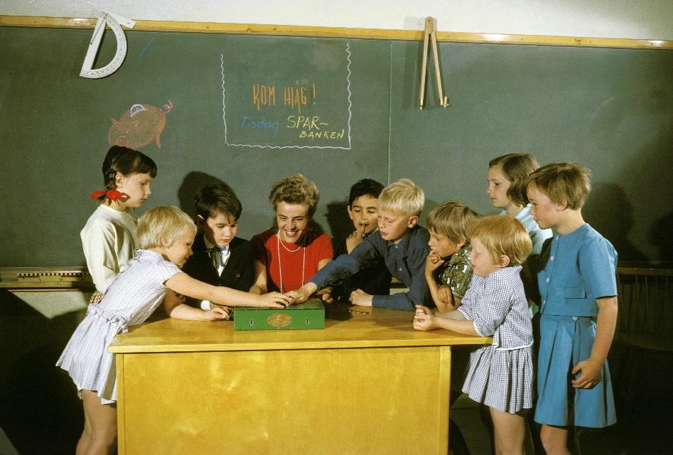 """Seriebild L 4 a, alt 1. Skolsparsituation i klassrum i Bergshamraskolan, Solna. Barnen lägger sina pengar i skolsparbössan under lärarinnans överinseende. På svarta tavlan står uppmaningen. """"Kom ihåg! Sparbanken"""""""