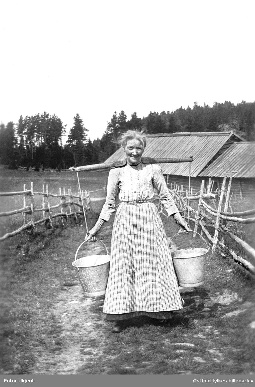 NIna Sørensen bærer vann, ca. 1920-1930. Opplysning 1996 fra barnebarnet til avbildete, kvinna heter Nina Sørensen, fra Rokke i Berg sogn. Tidligere opplyst til å være Mina Hansen, Ulveholtet under Bunes,