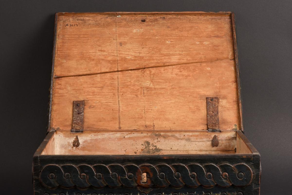 Rektangulärt furuskrin med plant lock. Skrinet är målat mörkgrönt och lockets karvsnittsdekor är rödmålade. På locket finns årtalet 1805 och initialerna JOD målade i vitt och rött. På fram- och kortsidorna dekor av skurna bandflätor i dubbla rader. De smidda järnbeslagen är delvis utformade som hjärtan.