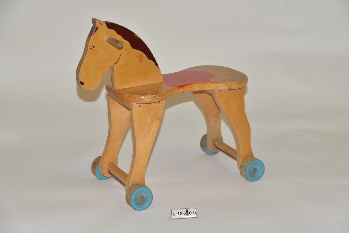 Pallhäst på hjul, tillverkad av massivt trä. Röd sadel, brun man och blå hjul, i övrigt naturfärgad.
