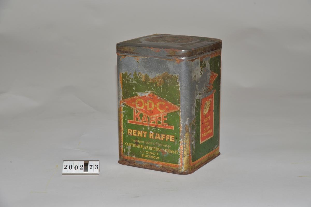 """Grön, gul och röd. Text """"1 kg ODC kaffe  GOTT TILL SISTA DROPPEN"""" . ODC = AB Otto Dahlström & Co, Stockholm. Locket pryds av en stjärna. Burken är rostig och färgen avskavd. Från Arne Ekströms handelsmuseum."""
