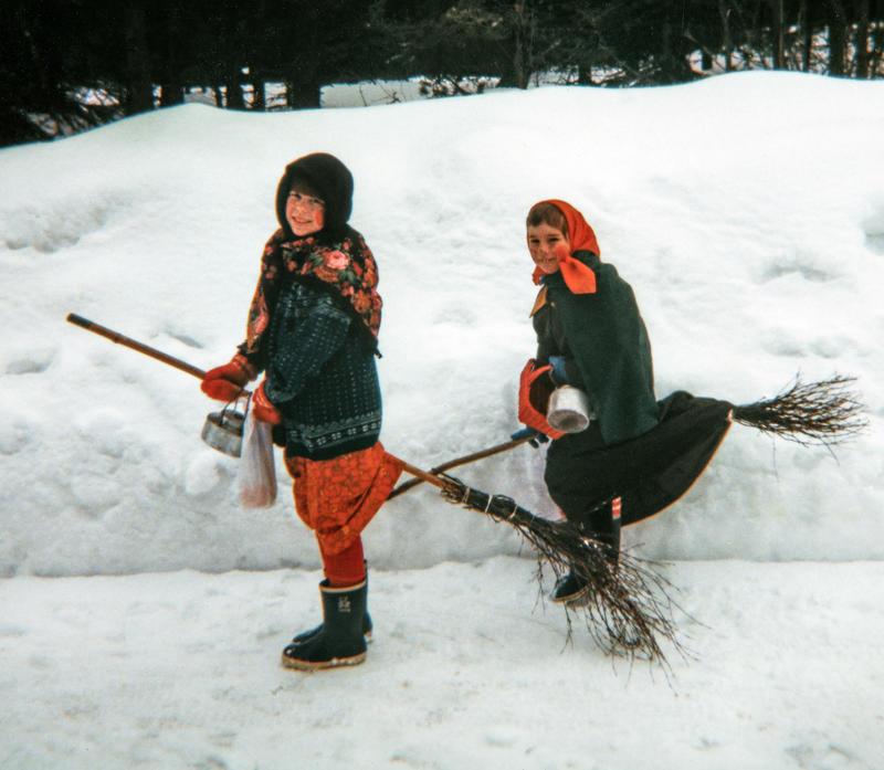 To jenter utkledd som gamle kjerringer med skaut på hodet står ved en snøkant med hver sin sopelime mellom bena, klare til å fly av gårde som påskehekser. (Foto/Photo)