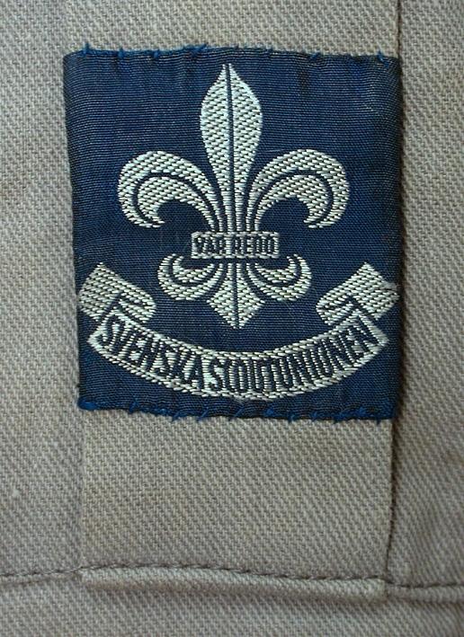 """Grå scoutskjorta i tjockt bomullstyg. 1 framstycke och 1 bakstycke (varav det senare är 55 mm längre än det förra) med 240 mm djupt sprund med isydd kil i vardera sida. Krage på stånd med 260 mm långt knapphålssprund som knäppes med 3 st gulbruna plastknappar märkta med franska liljan och texten """"VAR REDO"""" (scouternas motto). 3 st fastsydda lappar i nacken. Den ena med texten """"MAS OCH MYA SANFOR krymper icke"""", den andra med siffran 5 (storleken), den tredje med texten """"Scout DEPOTEN"""". 2 st bröstfickor knäppta med samma knappar som i halssprundet. På vänstra fickan  påsytt marinblått märke med grått invävt mönster i form av franska liljan """"VAR REDO"""" samt en banderoll med texten """"SVENSKA SCOUTUNIONEN"""". I samma ficka ligger en visselpipa i metall fästad i svart tvinnat snöre. Sleif med knäppning på vardera axel. På vardera sleif fastsytt grått märke med röd triangel med franska liljan inuti. Hellång, något avsmalnande, ärm med manschett och knäppning med 1 knapp. Veck mot manschetten. På vänster ärm stort marinblått märke med franska liljan """"SSU"""" samt banderoll med texten """"VAR REDO"""". På höger ärm 4 st mindre fastsydda märken varav det ena med texten """"ARVIKA""""."""
