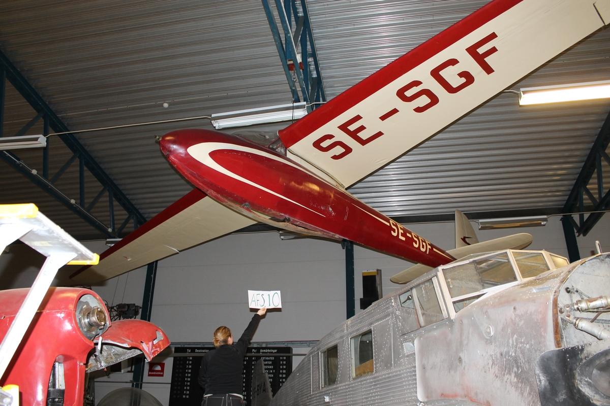 Segelflygplan av modell DFS Olympia. Ensitsigt plan med täckt kabin. Landstället består av en trämede med amortisörer mellan mede och undersidan av flygkroppen. Rödmålad med gulvit dekor.