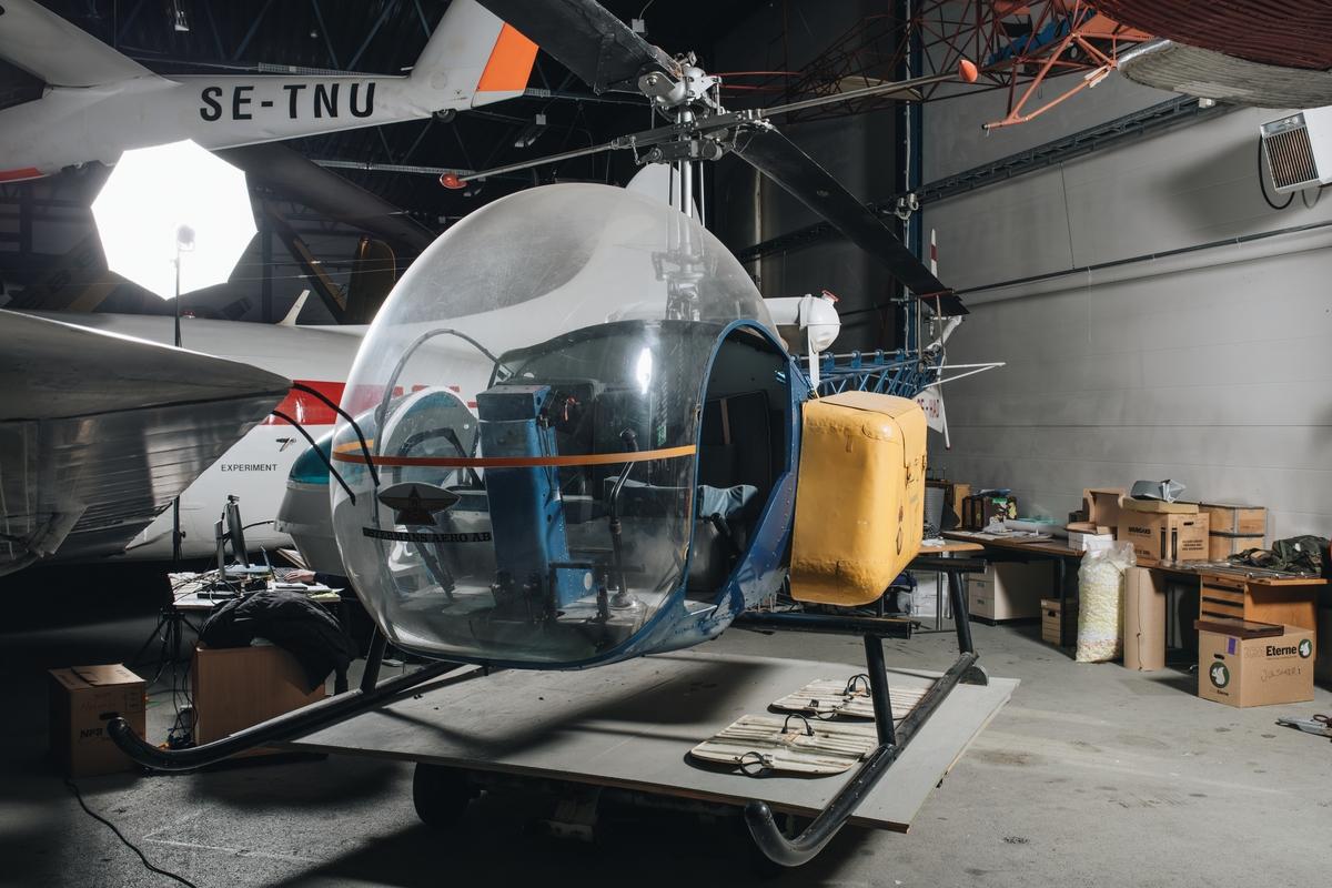 Helikopter av modell Bell 47, tvåsitsig. Blåmålad framkropp och stjärtbom. Landningsstället består av två medar. En gul postlåda med en karta över postrutten i Stockholms skärgård finns monterad på vänster sida. En annan postlåda (dock utan karta) finns förrådsställd. På vänster sida är en bår avsedd för sjuktransporter monterad.
