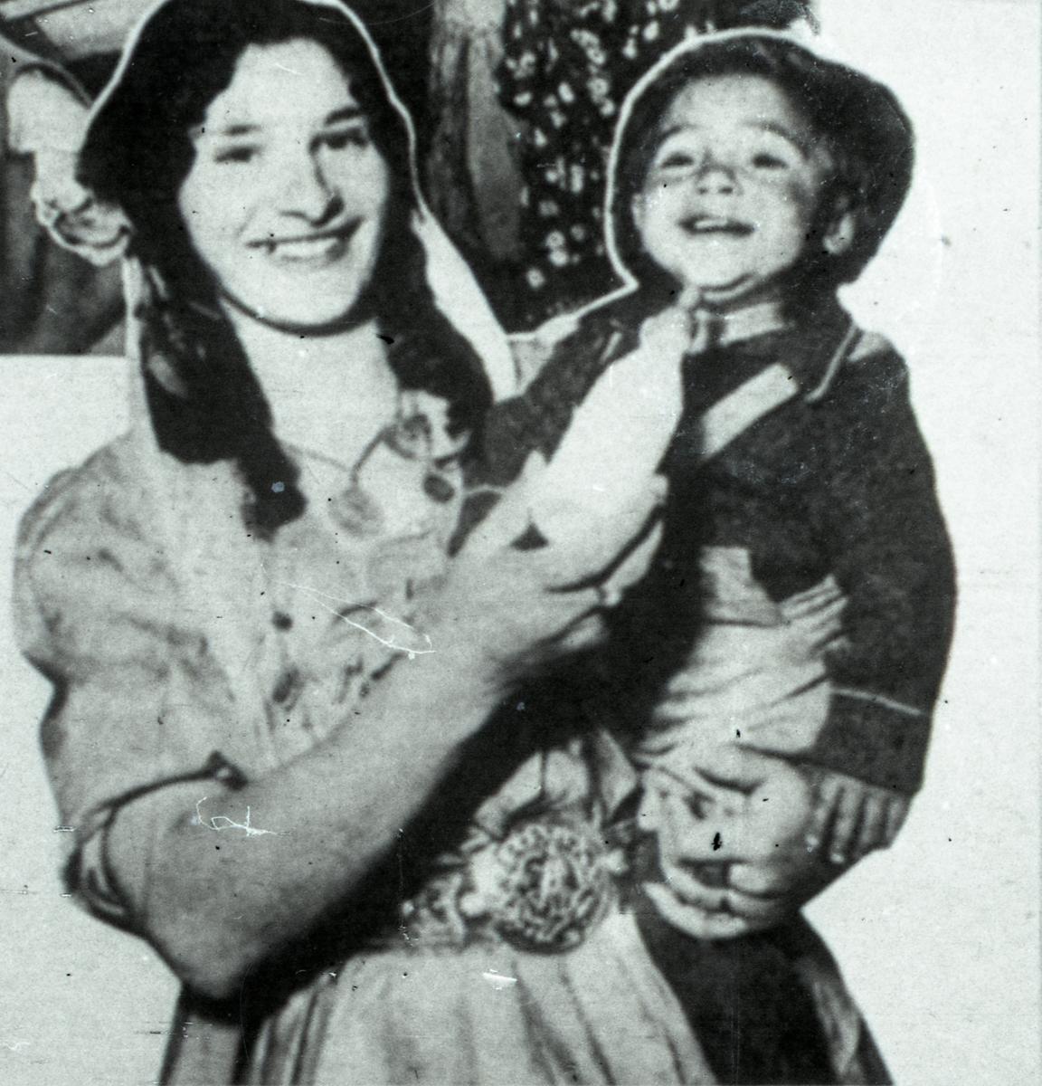 En kvinna står med ett barn i famnen. I handen håller hon en nappflaska. Bildens ursprung är okänt, men troligen är den ett avfotograferat tidningsklipp.