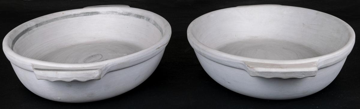 Två stycken formar, av oglaserat porslin. Grå färg. Oval form med skivhandtag. En form med dekor Blått band.