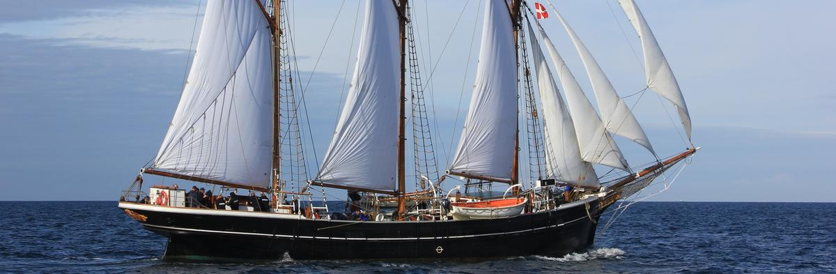 Sort seilbåt med tre master og fulle seil, mot blått hav og blå himmel. (Foto/Photo)