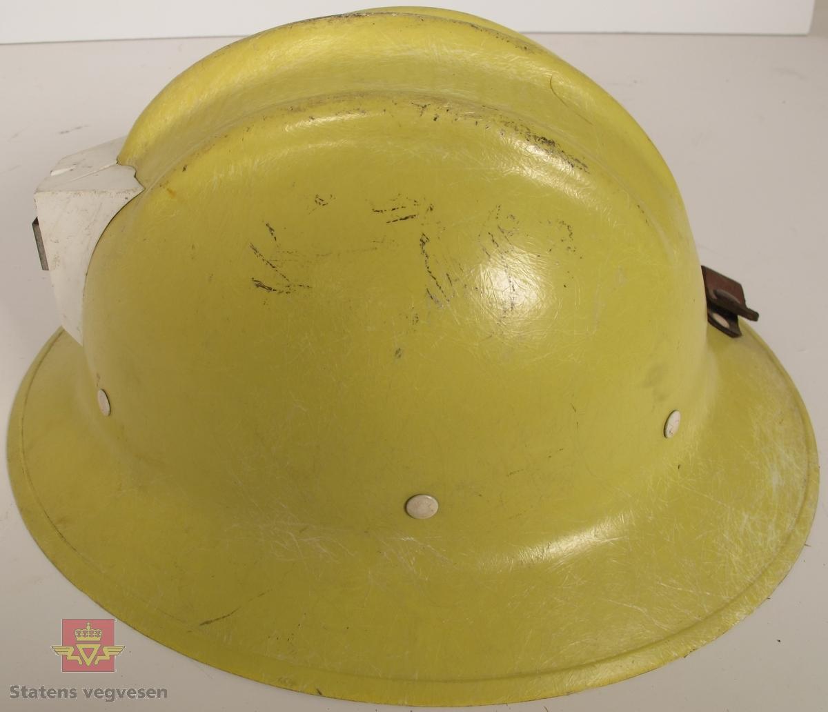 Gul vernehjelm i glassfiber med innmat av lær og tekstil. Feste for hodelykt foran og lærreim med trykknapp bak. Klistremerke i hvitt og blått med påskriften KRAFTLAGET OPPLANDSKRAFT bak på hjelmen, og navnet Asle skrevet inni hjelmen. Innskrifter på hjelmen: POLYGLAS LUPI MILANO ITALIA, E.D BULLARD CO. S.F-USA og HARD BOILED.