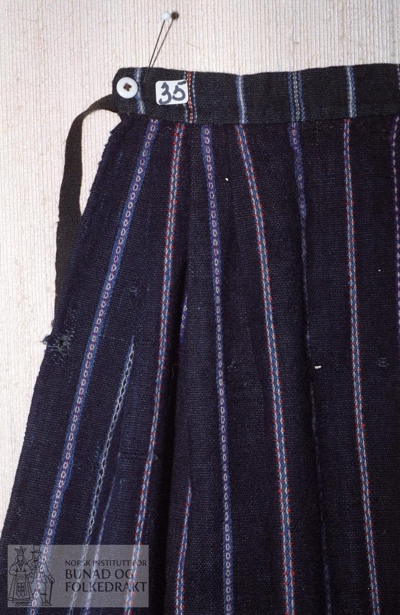 Materiale:  Renning:  mørk blå bomull. Innslag:  entråds mørk blått ullgarn. Forkleet har totalt 22 striper i enkel krokbragd, 5 ulike border. Symetrisk fra midten. Mønsterfarger i mellomblått, lilla og rødoransje ullgarn og kvitt bomullsgarn. Montering:  3 legg som ligger utover i hver side, ca. 2 - 3,5 cm dype. 3 cm glatt stykke i hver side. Glatt stykke framme, 11,5 cm. Linning:  3 cm brei linning av annet smalstripa forklestoff. Liten knapp i hver side. Skoning:  6,5 cm brunt bomullsstoff.   Lengde:          71 cm. Bredde:          62 cm. Bredde oppe:   31,5 cm. Lengde linning:  25 cm.