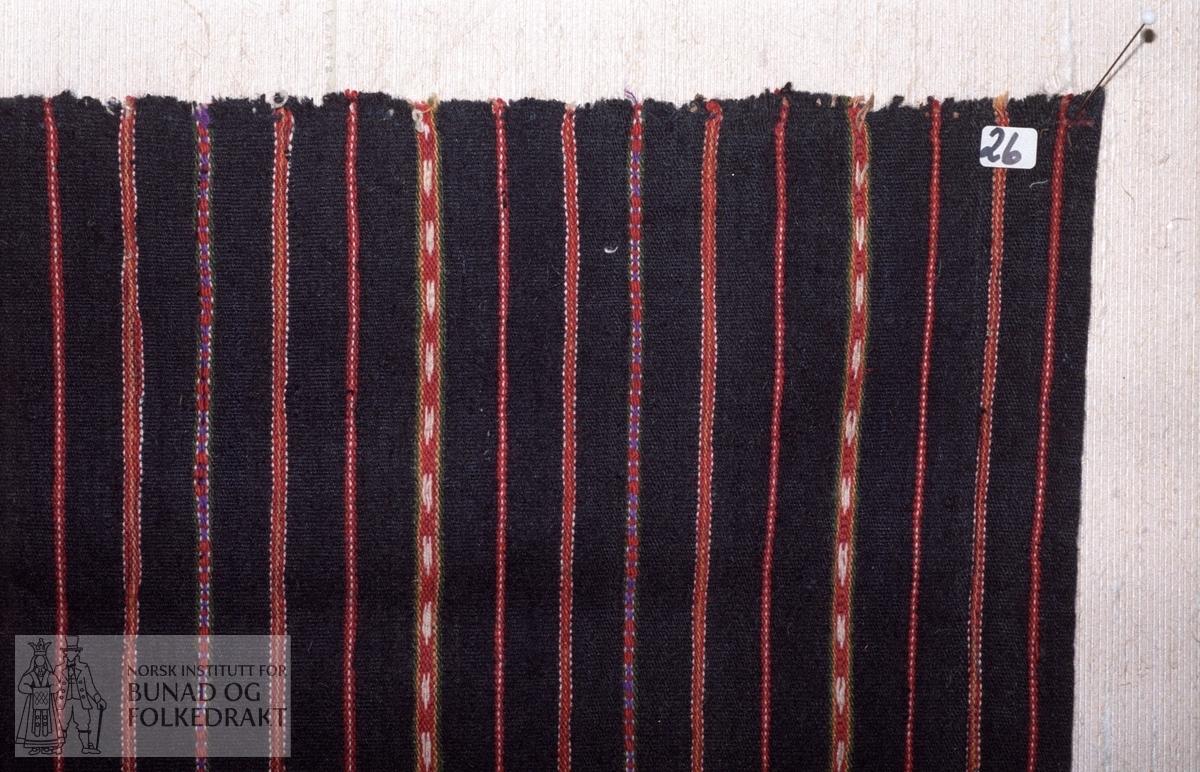 Materiale:  Renning:  mørk blå bomull. Innslag:  entråds svart ullgarn. Mønster:  smalstripa i toskaft, tavlebragd og halvsmett. 31 striper symetrisk i fargene rød, gul, grøn, lilla og kvit bomull. Montering:  4 cm skoning i bomullsstoff. Linninga er spretta av.  Lengde:  72 cm. Bredde:  69 cm.