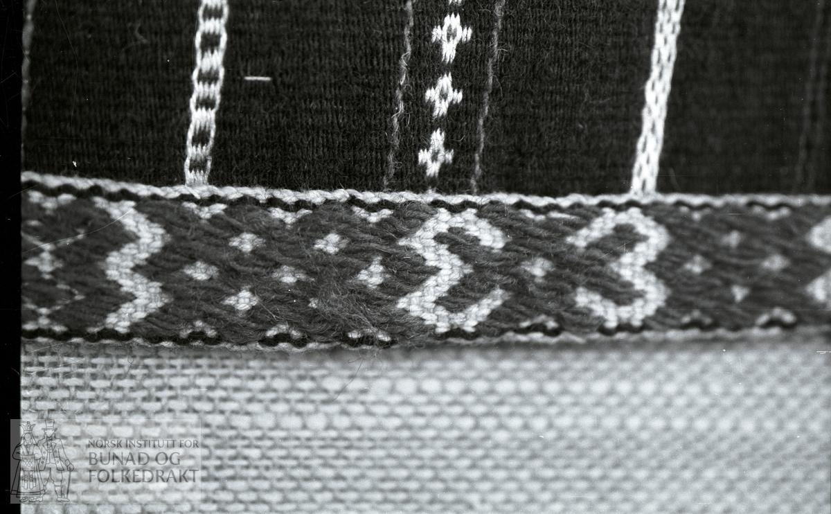 Nordhordlandsmessa 1974 - - - - - Vevd med ull innslag, hvit bomullsrenning. Svart bunn, mønster i turkis og gul ull, rød og hvit bomull. Border og striper. Grindvevd bånd nederst med opp-plukk. Hvit bomull og rød og svart ull. Linning tatt av. Br. 71 cm. H.: 73,5 cm, derav båndet 2,5 cm. Håndsydd.