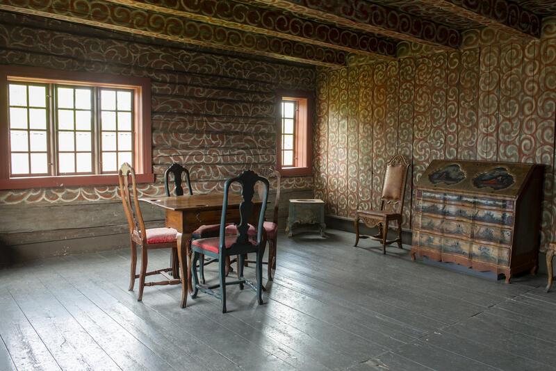 Interiør fra Bolstadbygningen viser en stolgruppe og en kiste i et rom med dekormalte tømmervegger.