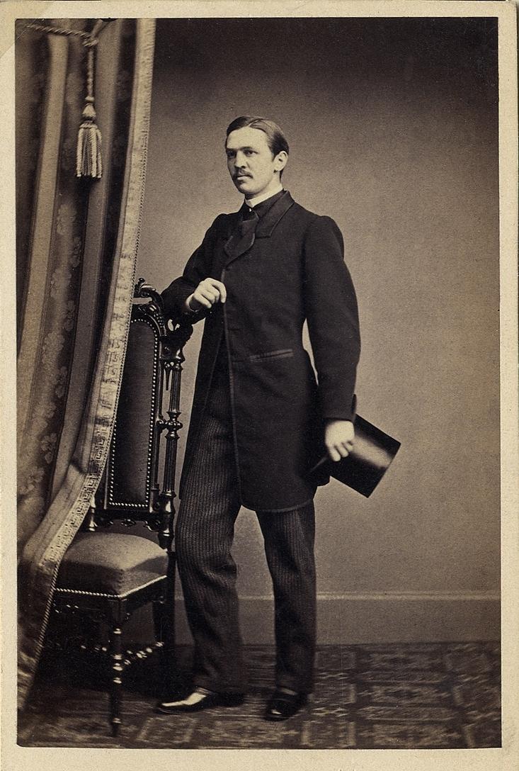 Foto av en man med mustascher, klädd i redingot med väst, stärkkrage, fluga och hög hatt. Han stöder ena armen  mot ryggstödet på en högryggad stol.  Helfigur, halvprofil. Ateljéfoto.