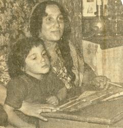 En kvinna och ett barn sitter tillsammans i en skolbänk. Bil