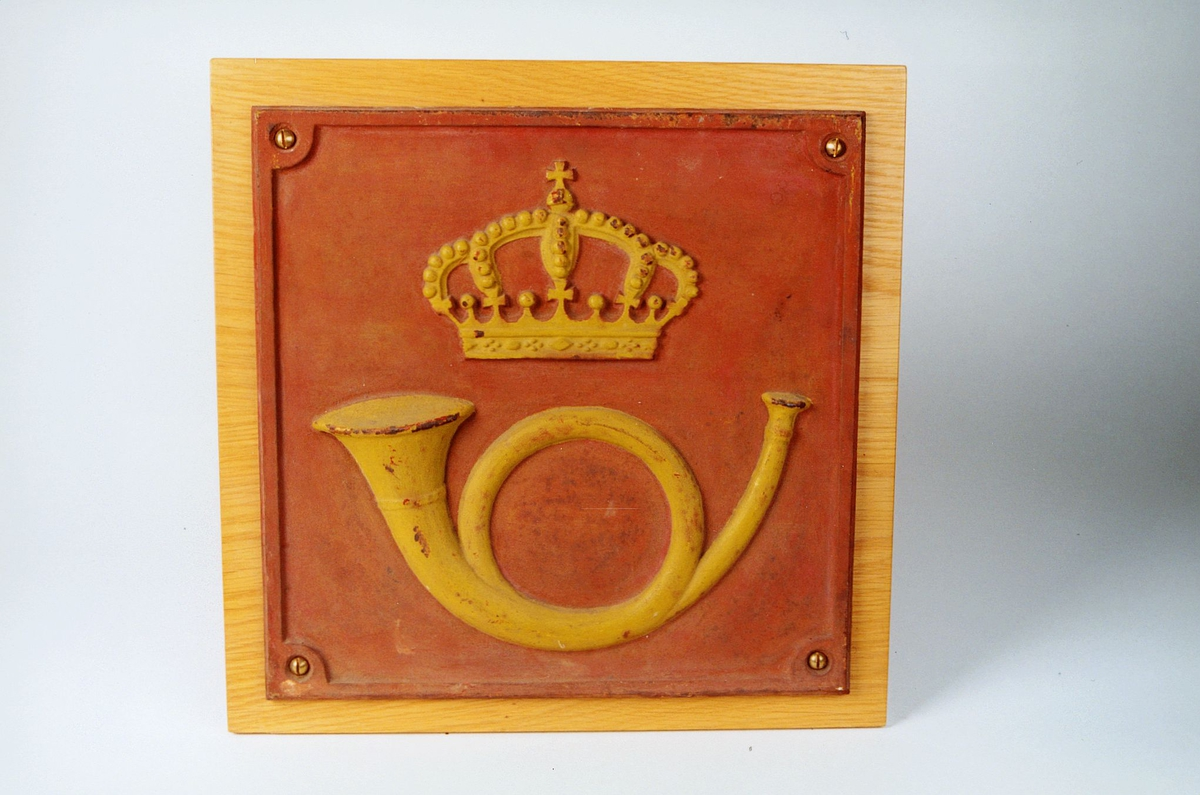 Postskilt av støpejern, rødmalt med gulmalt postemblem og kant. Med krone uten løve.