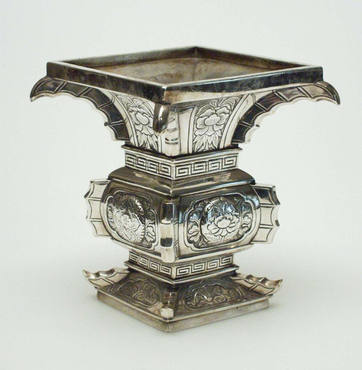 Firkantet vase i sølv dekorert med forsiringer og meanderborder (a ´la´greque). Utsvungen hals.