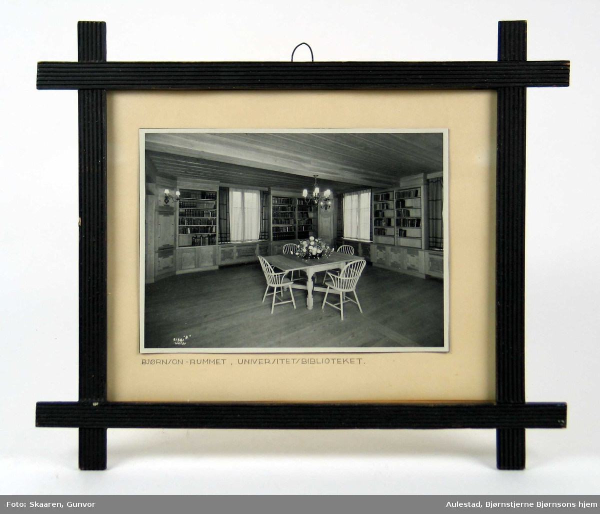 Fotografi limt på lys kartong og rammet inn med glass og svart treramme med riller. Hjørnene er lagt i kryss.