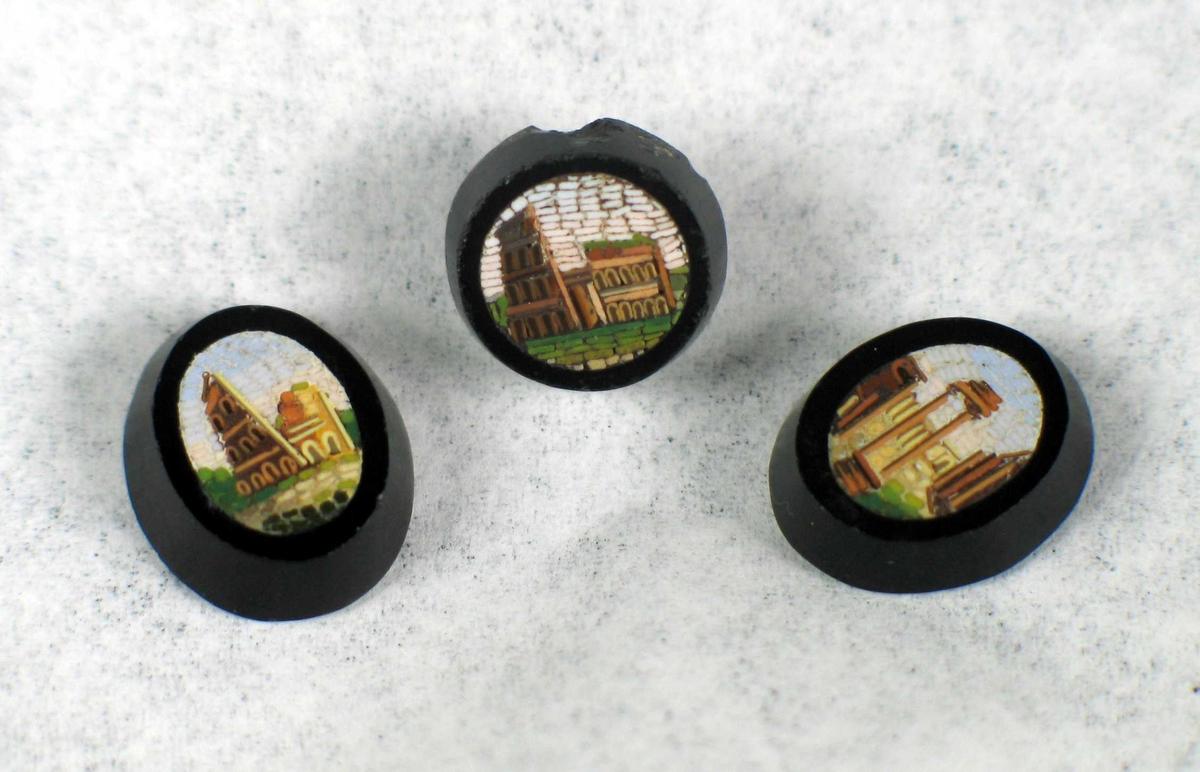 En rund og to ovale svarte knapper i stein med innlagt dekor i mosaikk. Motivet er ruiner fra antikken.