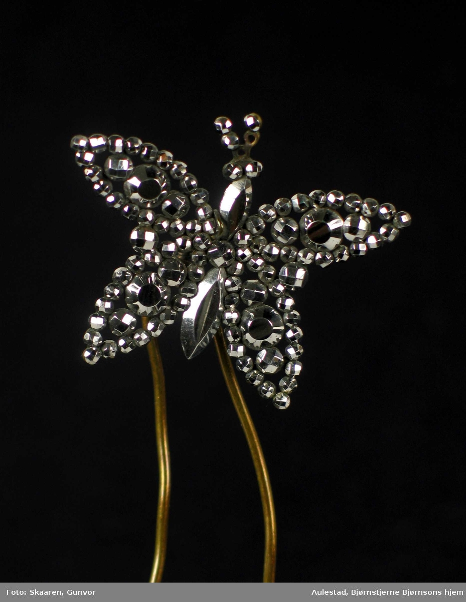 Hårpynt i metall formet som en sommerfugl. Innfeldt dekor.
