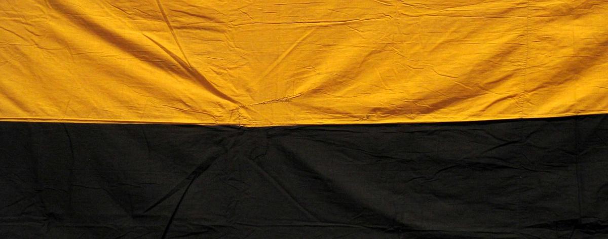 Banner sydd sammen av gult og svart bomullstoff. To horisontale striper.