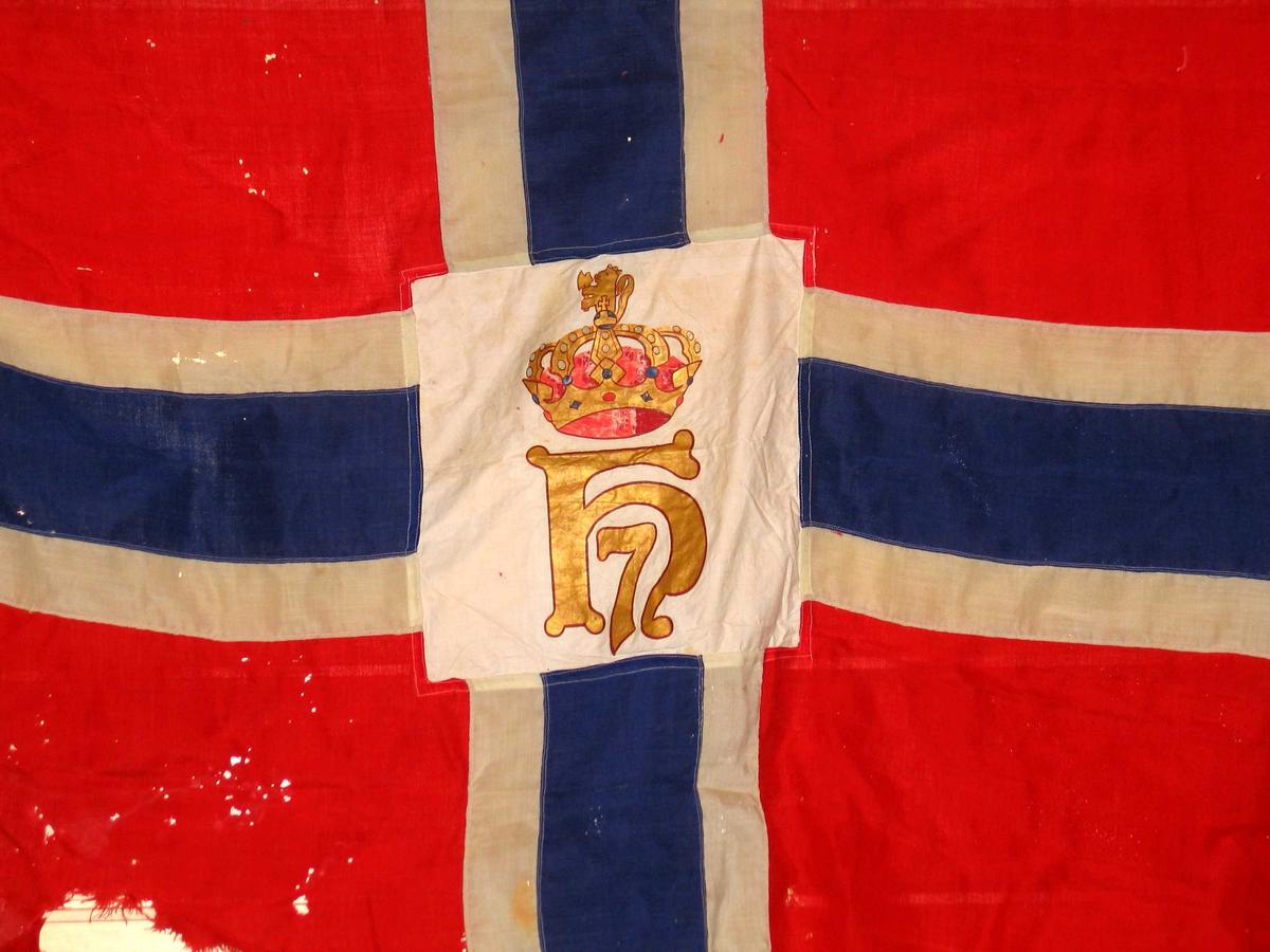 Norsk splittflagg med påsydd hvitt felt i midten. Motivet er trykt med silkestrykk i gull, rødt og blått. Motivet vises speilvendt på andre siden. Løpegang med snor og metallring.