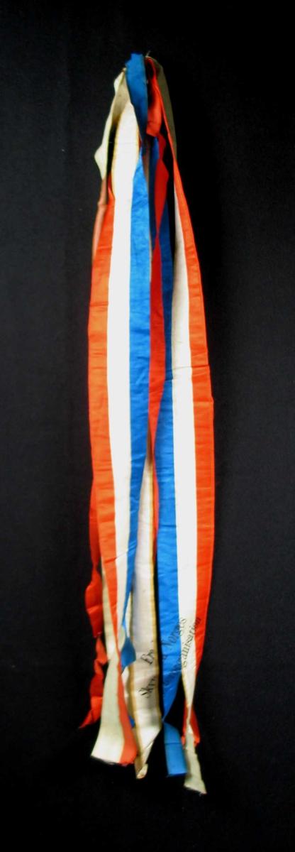 Begravelsessløyfe i rød, hvit og blå og silke.