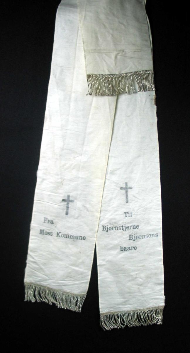 Begravelsessløyfe i hvit silke med sølvfrynser.