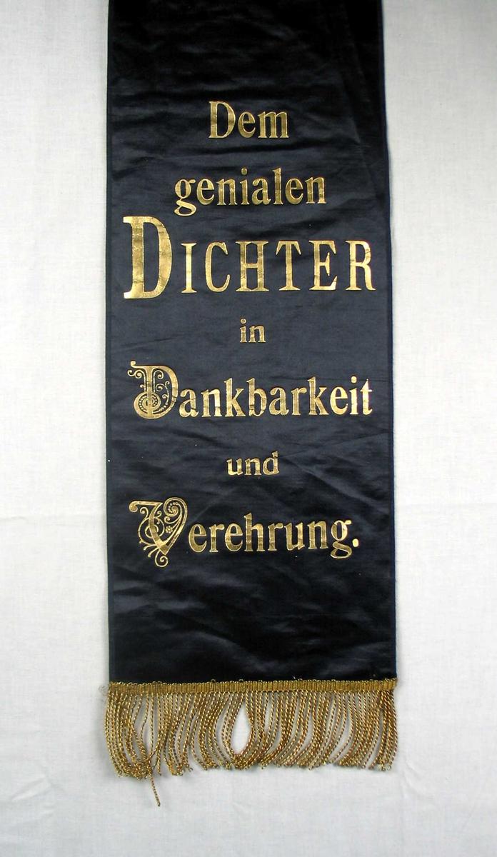 Begravelsessløyfe i svart silke med frynser og tekst i gull.
