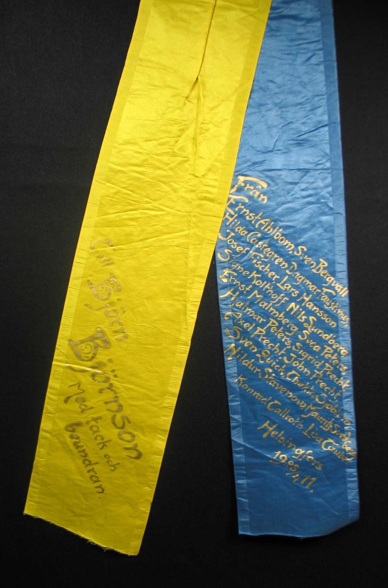 Begravelsessløyfe i blå og gul silke med tekst i gull.