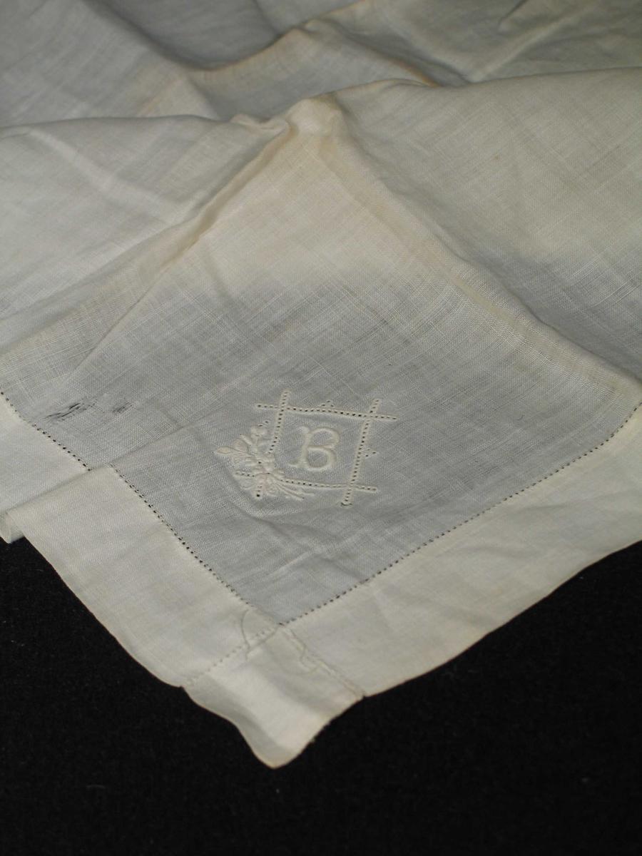 Hvitt lommetørkle i lin med stikkhullfald. Broderi: B i tykksøm, satt inn i en rektangulær ramme av tett rad hullet søm. Blomsterbukett i nedre venstre hjørne av plattsøm. Mål: 3x3 cm. I motsatt hjørne merke med blått garn.