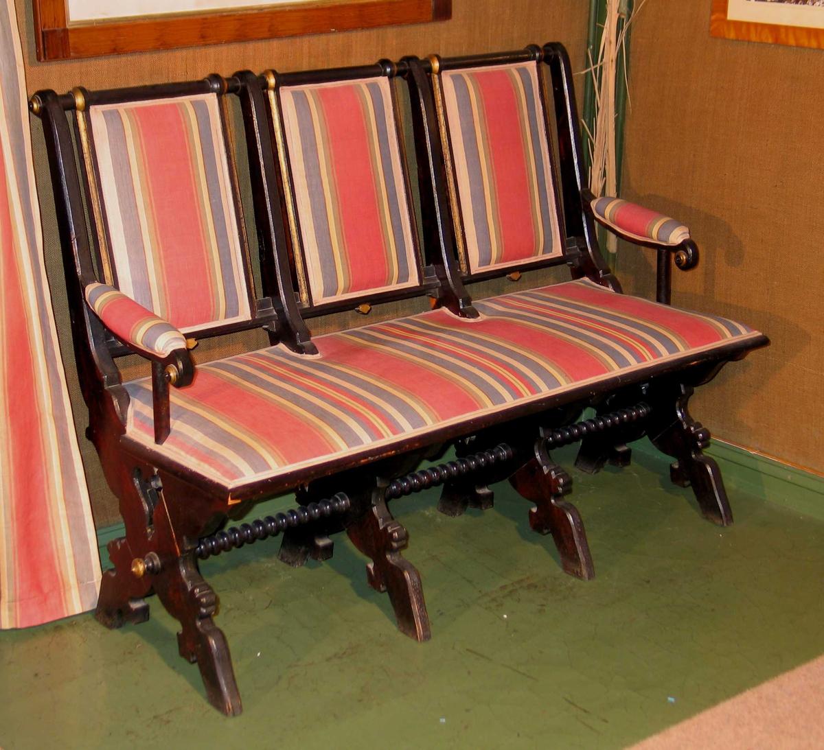Svartmalt benk satt sammen av tre stoler. Kraftige profilerte bukkeben med kuledreid sprosse mellom. Rygg og sete trukket i et flerfarget stripet stoff. Gullmalte detaljer på rygg og sprosse. Stoppet armlene.