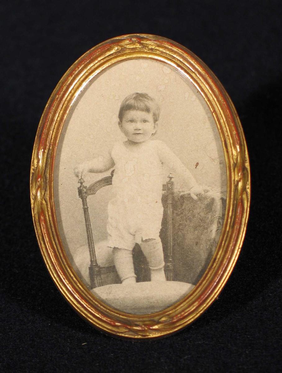 Et lite barn fotografert i atelier. Står på en stol.