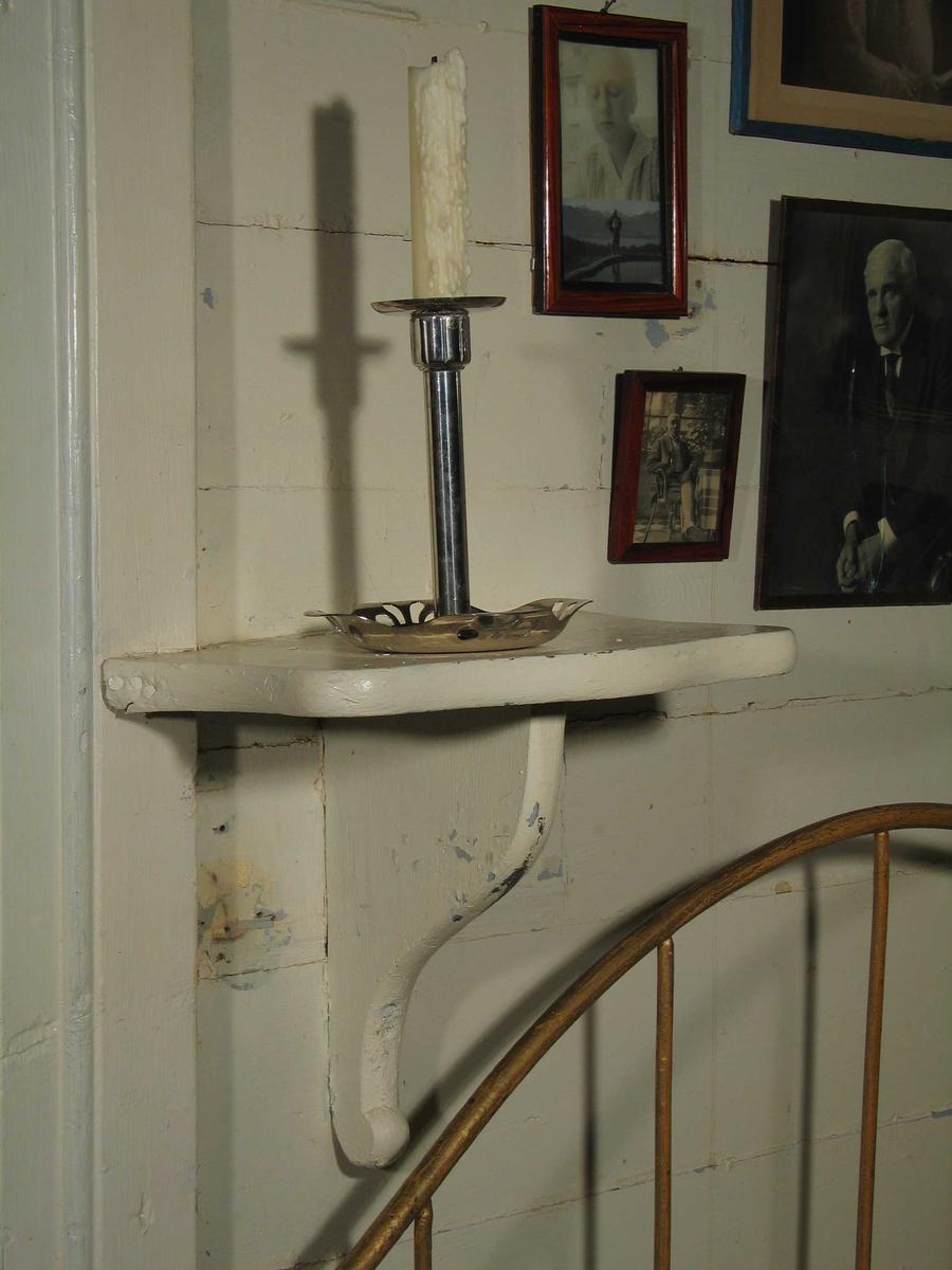 Hvitmalt hylle i tre med buede sider og knekt under. Spikret fast til veggen.