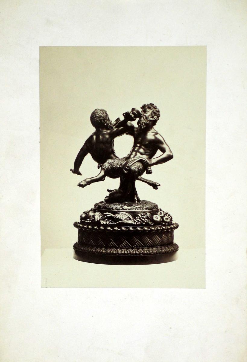 Fotografi av en skulptur: To djevelskikkelser arm i arm med drikkebeger. Rundt dekorert fotstykke med vindruer, ananas og epler. Fotografiet er limt på kartong.
