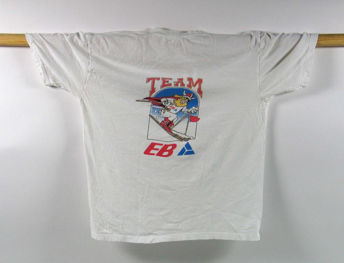 Hvit t-skjorte. Foran er det en logo for de olympiske vinterleker på Lillehammer i 1994. På ryggen er det en logo for TEAM EB. I denne logoen inngår det et motiv av en viking på ski.