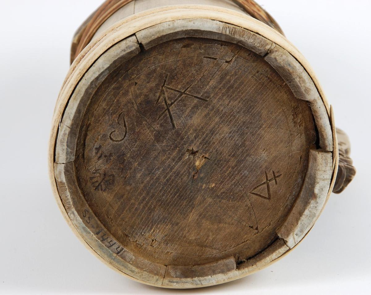 Kanne av bjørkestaver. Lokk med geometriske felter. Hanken er skåret ut av en av stavene, tre utskårete hoder, hulkildekor. Korpus med fire gjorder oppe og fem nede, under seksbladrose og buemerke.