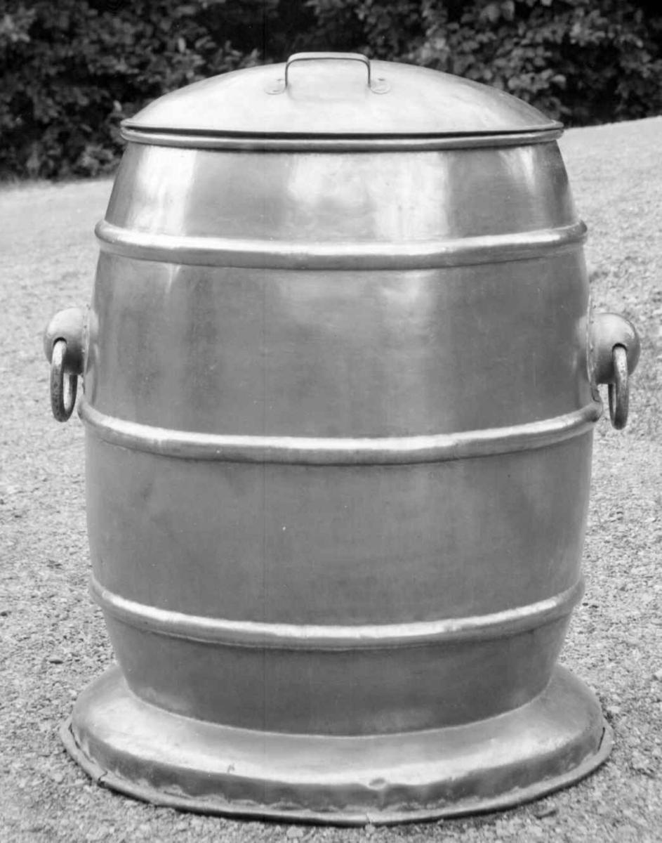"""Tønneformet vannbeholder av kobber. Hank på hver side og håndtak på det delte lbuede okket. tre """"liksombånd"""" på tønna."""