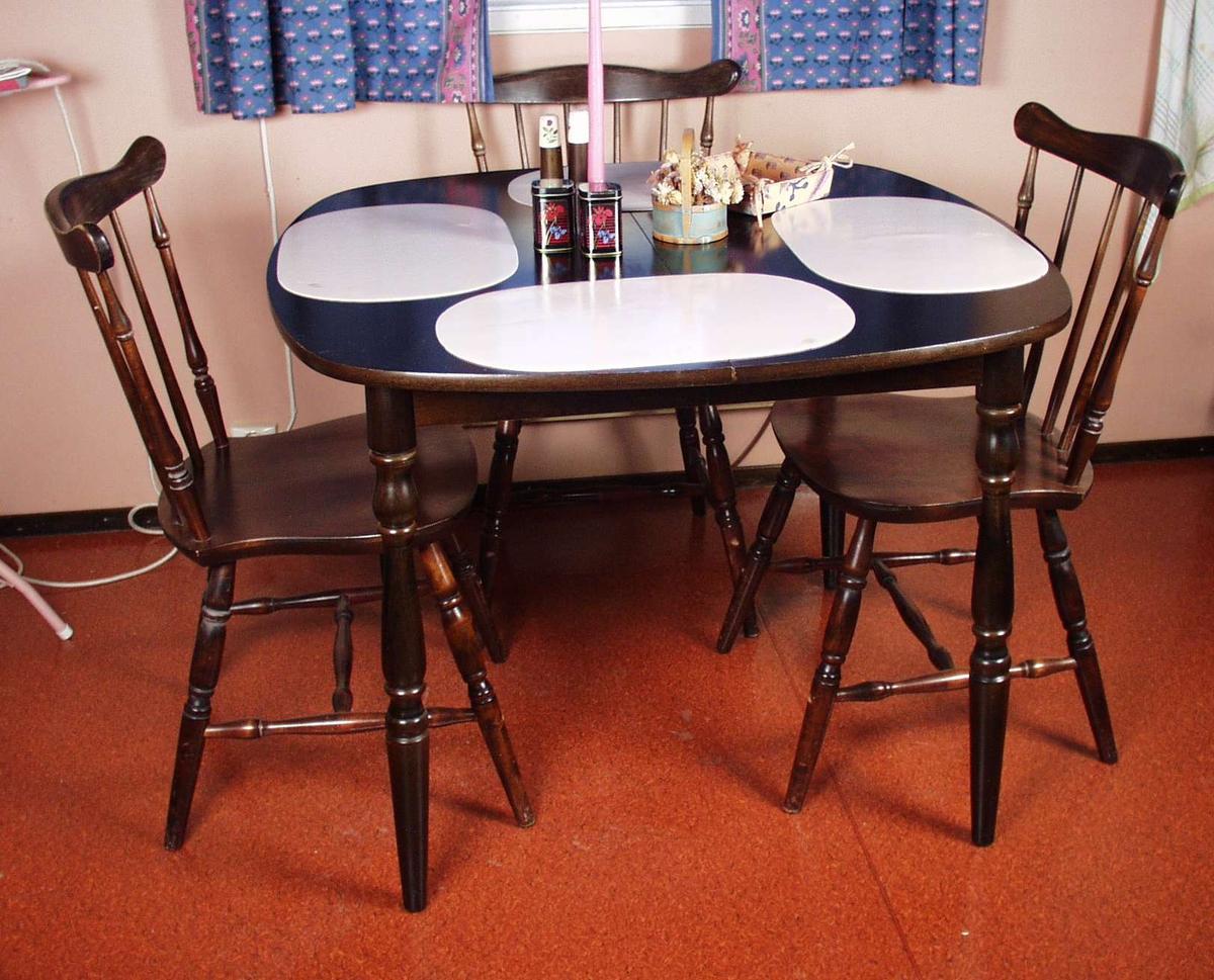 Kjøkkenbord i mørkt treverk med dreide ben. Bordet er firkantet med avrunda hjørner.