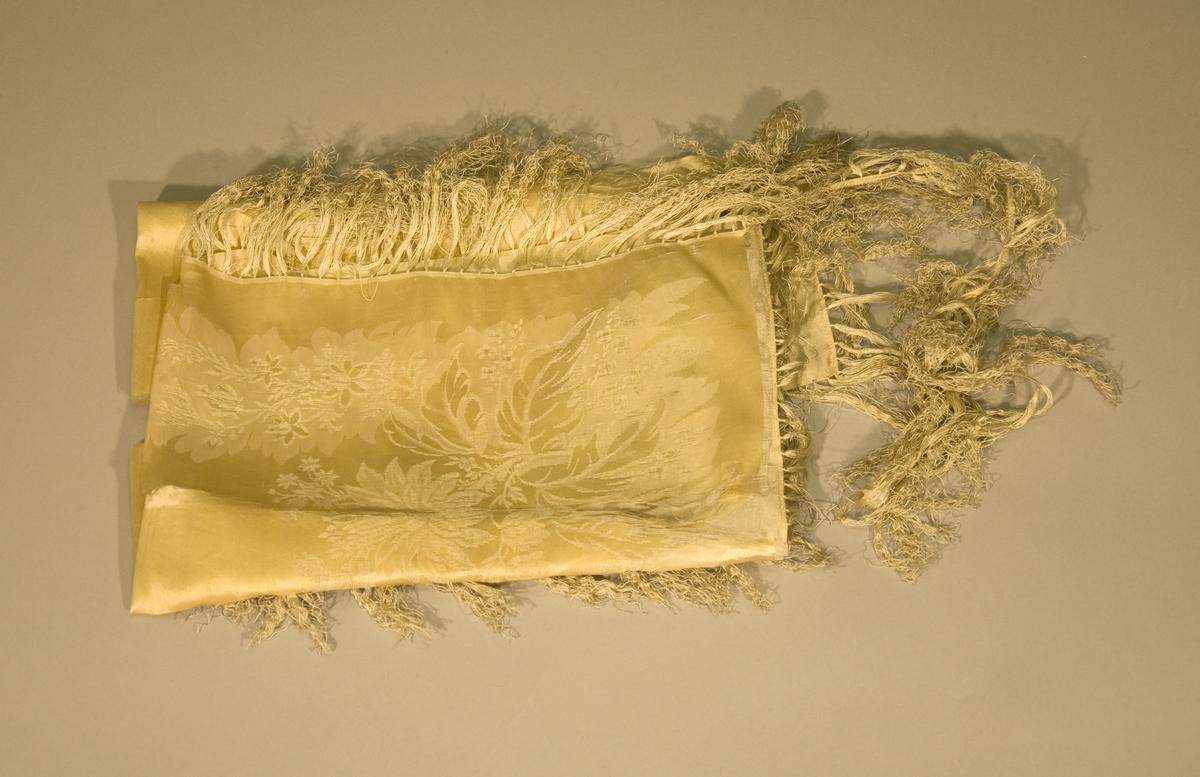 Gult tørkle av mønstervevd silke. Tørkledet har maskinsydd fald og er påsydd silkefrynser, 11 cm. I svært dårlig stand, falden og frynsekanten er delvis løsnet fra tørkledet.