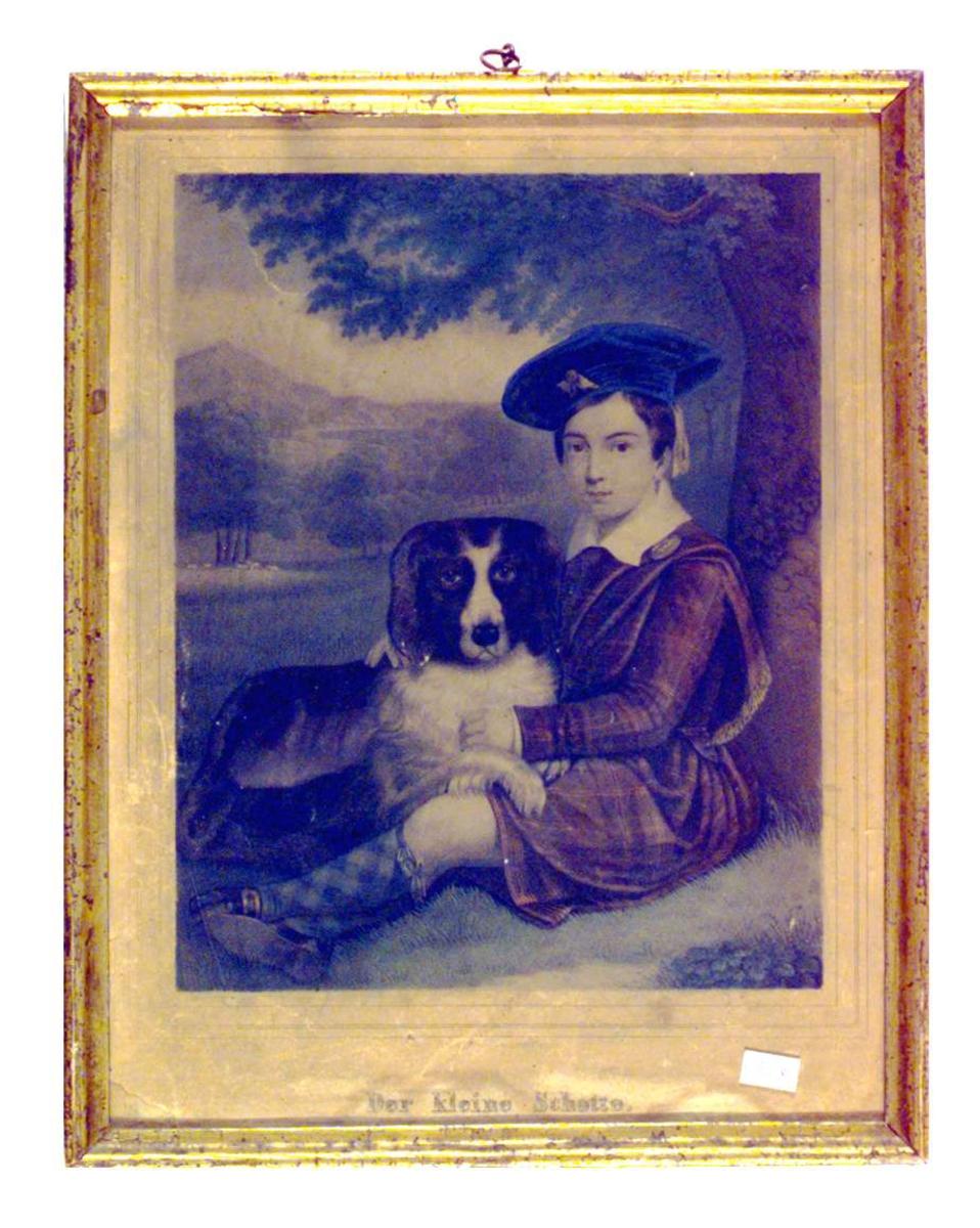 En ung gutt i skotsk drakt sitter under et tre med en hund på fanget.