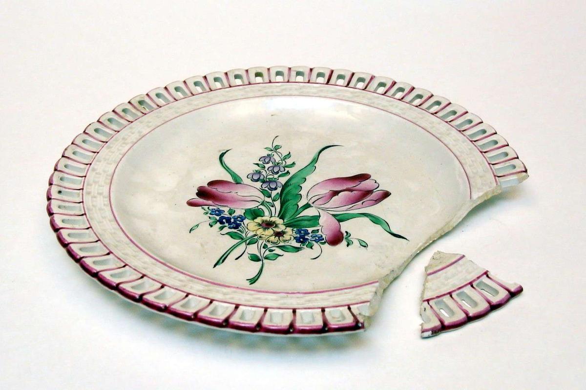 Tallerken i keramikk med kremfarget glasur og med blomsterdekor. Den har 'hullfallskant'. Den er stemplet Demi-porcelaine, Luneville, France, med bokstavene K og G rundt en krone.Tallerkenen er limt og mangler et skår.